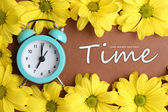 Alarm clock and beautiful flowers on brown background — Foto de Stock