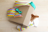 Unwrapped and opened gift box  on wooden background — Stock Photo