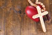Srdce s růženec na dřevěné pozadí — Stock fotografie