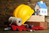 组成与安全头盔、 皮手套、 工具和木制背景装饰房子 — 图库照片