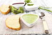 Bowl of broccoli soup on table — Stock Photo
