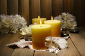 Beautiful candles with flowers on wooden background — Stock Photo