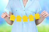 Woman hold houses on natural background — Stock Photo