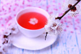 ароматный чай с цветущими ветвями на деревянный стол крупным планом — Стоковое фото