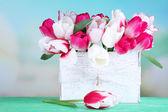 Beautiful tulips  in wooden box, on light background — Stockfoto