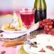 Assorted cheese plate , grape and wine glass on table, on light background — Stock Photo #44739323