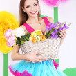 Beautiful young woman in petty skirt holding basket of flowers on decorative background — Stock Photo