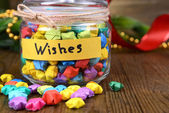 Paper stars with dreams in jar on table close-up — Stock Photo