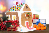 Beautiful gingerbread house with Christmas decor on wooden table — Stock Photo
