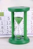 Hourglass and calendar close-up — Stock Photo