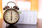 Alarm clock  and calendar on bright background — Stock Photo