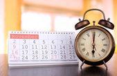 Alarm clock  and calendar on bright background — Stock Photo