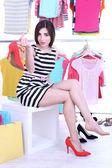 Mladá žena se snaží na boty v obchodě — Stock fotografie