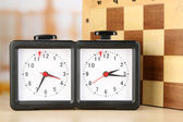 Chess clock and board on light background — Foto de Stock