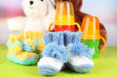 Composition with crocheted booties for baby, bottle, toy and other things on color background — Stock Photo