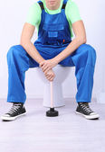 Plumber with toilet plunger on light background — Stock Photo