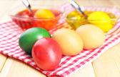 Taças com tinta para páscoa ovos e ovos, close-up — Fotografia Stock