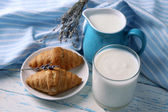 Homemade yogurt in jug and tasty croissants on wooden table background — Stock Photo