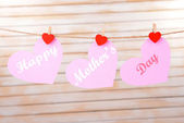 Happy Mothers Day message written on paper hearts on light background — Stock Photo