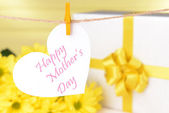 Happy Mothers Day message written on paper heart with flowers on yellow background — Stok fotoğraf