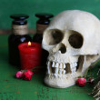 Composition with skull, and , magic potions, candle  on color wooden background — Stock Photo #44831315