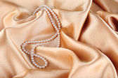 Beautiful pearls on golden silk cloth — Stock Photo
