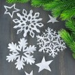 Beautiful snowflakes with fir branch on wooden background — Stock Photo #44966555
