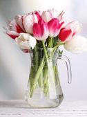 Beautiful tulips in glass jug on light background — Stock Photo