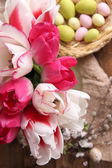 Composition with Easter eggs and beautiful tulips in glass jug on wooden background — Stockfoto