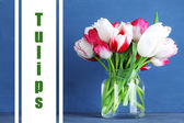 Beautiful tulips in glass jug on color wooden background — Stock Photo