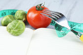 Book with measuring tape and vegetables on wooden background — Stock Photo