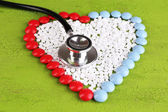Heart of pills and stethoscope on wooden background — Stock Photo