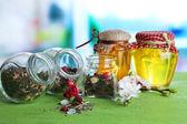 Variedade de ervas e chá em potes de vidro na mesa de madeira, no fundo brilhante — Fotografia Stock