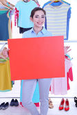 Beautiful young woman holding blank poster near rack with hangers — Stock Photo