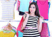 Beautiful young woman with paper bags near rack with hangers — Stock Photo