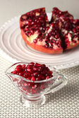 Ripe pomegranate on plate,  on light background — Stock Photo