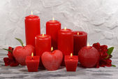 Beautiful candles with flowers on table on grey background — Stock Photo