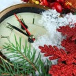 Clock with fir branches and Christmas decorations under snow close up — Stock Photo #45052687