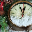 Clock with fir branches and Christmas decorations under snow close up — Stock Photo #45052689