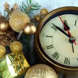 Clock with fir branches and Christmas decorations on wooden background — Stock Photo #45052691