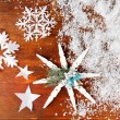Beautiful snowflakes with snow on wooden background — Stock Photo