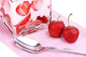 Glass of ripe strawberries with cream isolated on white — Stock Photo