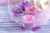 Prachtige kleurrijke kaarsen en orchideebloemen, op een houten achtergrond kleur — Stockfoto