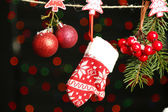 Santa mitten and Christmas accessories on black background with lights — Stock Photo