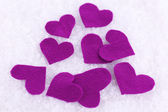 Little felt hearts on snowy background — Stock Photo