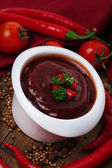 Tomato sauce in bowl on wooden table close-up — Stock Photo