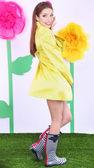 Hermosa joven en manto amarillo sobre fondo decorativo — Foto de Stock