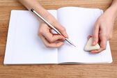 Mains humaines avec crayon écriture sur papier et effacement de caoutchouc sur fond de table en bois — Photo