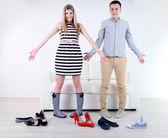 Loving couple choose new shoes, on light background — Stockfoto