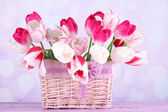 Beautiful tulips in wicker basket, on light background — Stock Photo